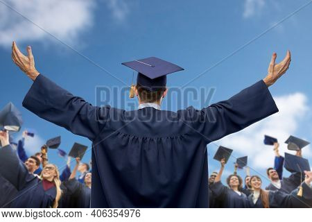 education, graduation and people concept - male graduate student over group of happy international students in bachelor gowns waving mortar boards or hats over blue sky and clouds background