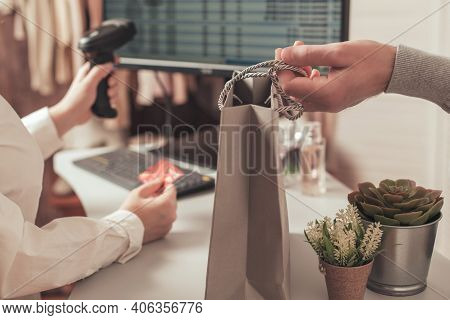 Man With Credit Card Buying Gift On Valentine's Day In A Female Clothing Store. Woman Cashier, Selle