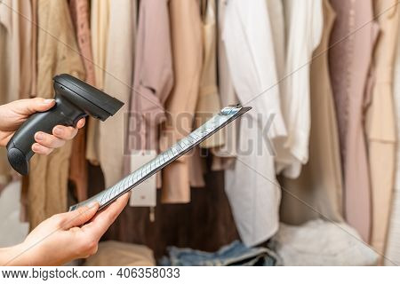 Female Entrepreneur Holding A Clipboard With Inventory List, Barcode Scanner While Doing Inventory I