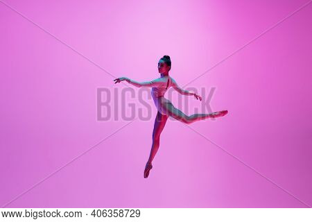 High Above. Young And Graceful Ballet Dancer On Pink Studio Background In Neon Light. Art, Motion, A