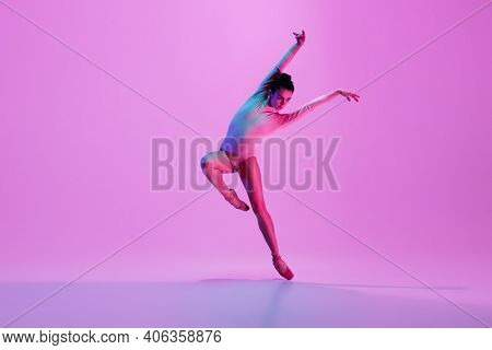 Inspiration. Young And Graceful Ballet Dancer On Pink Studio Background In Neon Light. Art, Motion,