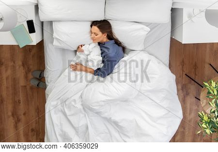 people, relax and comfort concept - young woman sleeping in bed at home