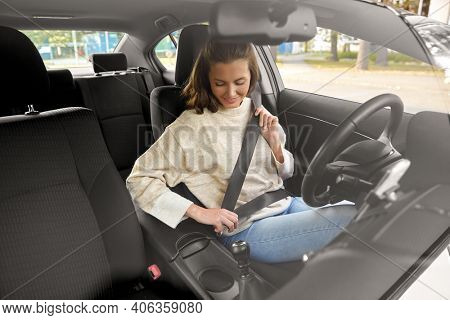 safety, car driving and people concept - happy smiling young woman or female driver fastening seat belt
