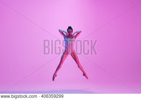 Flying On. Young And Graceful Ballet Dancer On Pink Studio Background In Neon Light. Art, Motion, Ac
