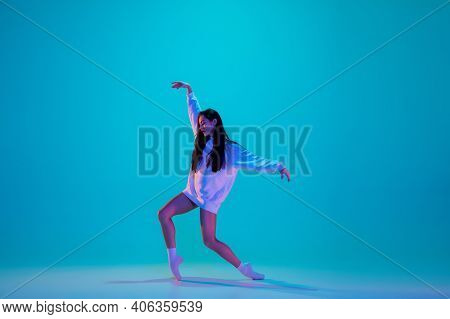 Inspired. Young And Graceful Ballet Dancer Isolated On Blue Studio Background In Neon Light. Art, Mo