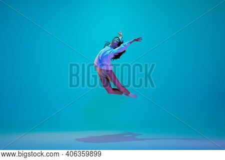 Flying. Young And Graceful Ballet Dancer Isolated On Blue Studio Background In Neon Light. Art, Moti