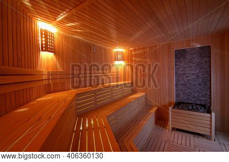 Seat In Sauna Room. Empty Wooden Steam Room With Stone Heater.sauna Room For Good Health. Sauna Room