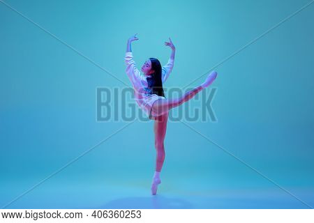 Dreamful. Young And Graceful Ballet Dancer Isolated On Blue Studio Background In Neon Light. Art, Mo