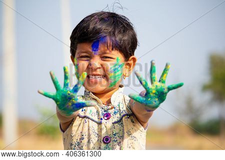 Young Cute Cheerful Little Girl Kid With Applied Holi Colors Powder Showing Colorful Hands To Camera