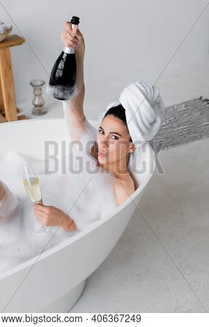 Young Woman With Champagne Looking At Camera In Bathtub With Lather