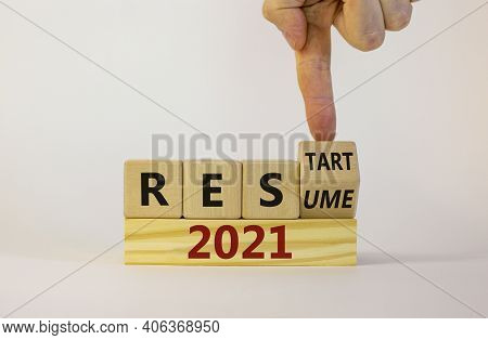 2021 Resume And Restart Symbol. Businessman Turns A Cube And Changes The Word '2021 Resume' To '2021