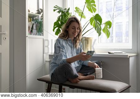 Smiling Woman Holding Cup Of Coffee, Using Mobile Smart Phone, Talking In Video Chat Or Social Netwo