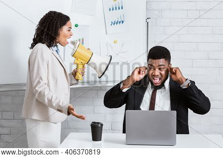 Enraged Female Boss With Loudspeaker Screaming At Her Scared Subordinate At Company Office. Frighten