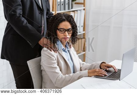 Sexual Abuse At Office Concept. Male Boss Putting His Hands On Female Employees Shoulders, Young Wom