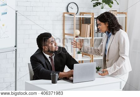 Angry African American Lady Boss Scolding Male Employee For Error In Urgent Project At Office. Displ