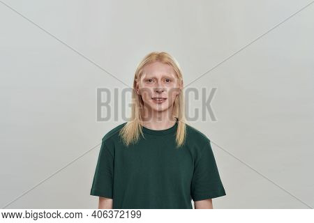 Handsome Young Caucasian Male Model With Long Fair Hair Smiling Uncertainly While Posing On Light Ba