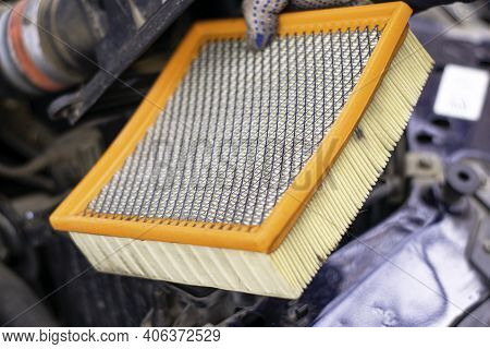 A Mechanic Removes An Old Dirty Filter Element From The Car's Air Filter Housing