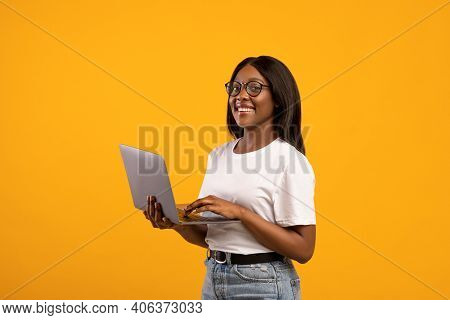 Happy African American Young Woman With Glasses Holding Newest Laptop And Smiling, Yellow Studio Bac