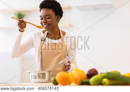Happy Black Lady Tasting Dinner In Kitchen Cooking Healthy Food Standing Near Table At Home. Nutriti