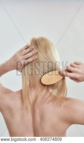 Young Shirtless Man Grooming His Long Blond Hair Using Wooden Comb While Standing Backwards To Camer