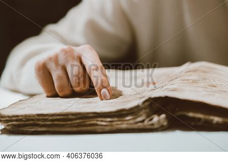 Woman Reading Ancient Book - Bible. Concentrated Attentively Follows Finger On Paper Page In Library
