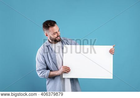 Happy Smiling Man Displaying White Blank Placard On Blue Studio Background, Mockup For Logo Or Desig