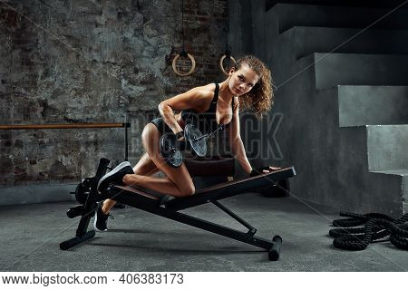 A Girl With Dumbbells Is Engaged In Bodybuilding On The Background Of The Gym , A Woman Is Engaged I