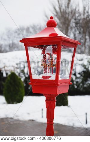 An Old Style Red Lantern With Christmas Merry-go-round Musical Box Decoration In It In A Snow-covere