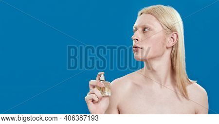 Young Caucasian Man With Long Blond Hair Holding Perfume Bottle Near Naked Neck While Standing On Bl
