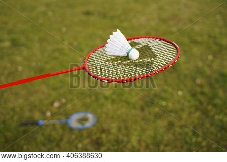 Badminton Rackets And Shuttlecocks Of Different Colors Are On Green Lawn