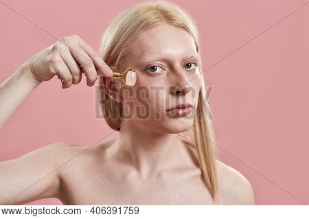 Portrait Of Young Caucasian Boy With Long Fair Hair Using Quartz Roller For Massage Under Eye While