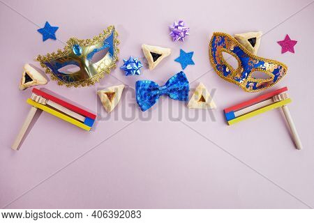 Purim Celebration. Hamantashen Or Haman Ears, Noisemaker And Mask On Grey Background. Top View