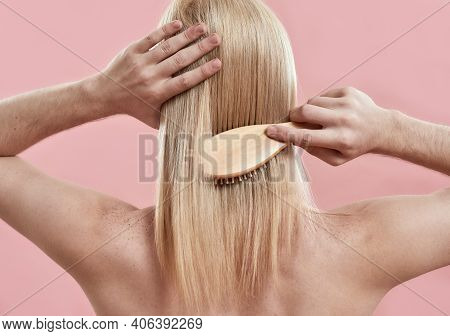 Young Man Combing His Long Blond Hair While Standing Backwards To Camera On Pink Background. Male Be