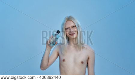Smiling Young Caucasian Boy With Long Fair Hair Holding Bottle With Mouthwash Liquid While Standing