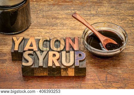 a small bowl of yacon syrup against rustic weathered wood with text in vintage letterpress printning blocks,  a powerful prebiotic sweetener derived from the yacon root