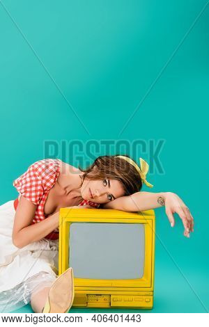 Fashionable Woman In Vintage Clothes Looking At Camera While Leaning On Yellow Vintage Tv On Turquoi