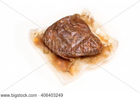 The semifinished pulled pork meat in the plastic foil prepared by the sous vide process isolated on