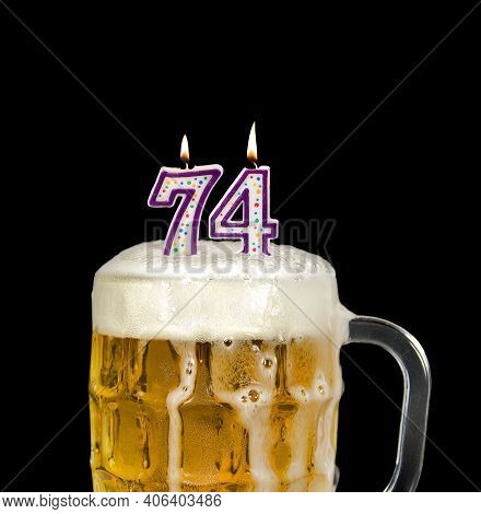 Number 74 Candle In Beer Mug For Birthday Celebration Isolated On Black