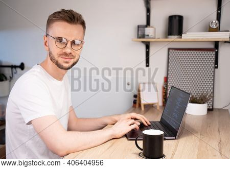 Portrait Of Male Programmer Using Programs Computer Code In A Bright Home. Concept Programmer Day.