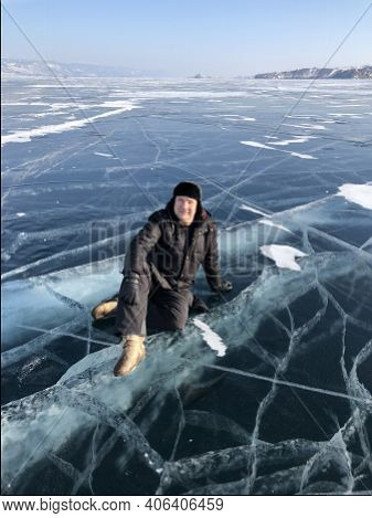Tourist Sitting On The Surface Of The Cracks Of The Frozen Lake Baikal In The Winter Season In Siber