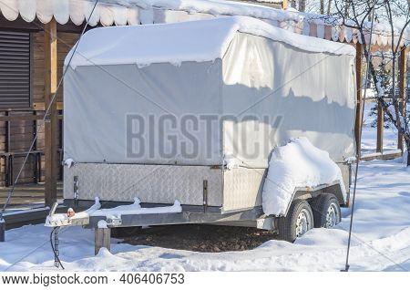 Motorhome Rv, Trailer, Campervan Parked Near House Under Snow In Winter.