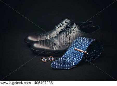 Blue Rolled Necktie, Stylish Tie Pin, Cufflinks And Fashionable Black Men's Shoes On Dark Background