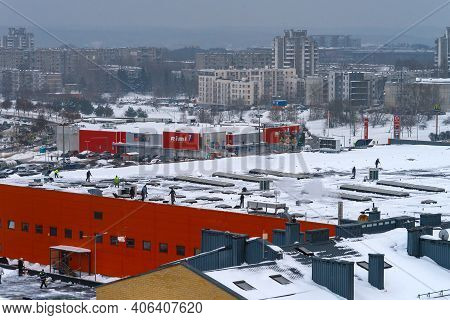 Vilnius, Lithuania- February 03, 2021: Workers Cleaning Roof Of Shopping Center Building From Snow W