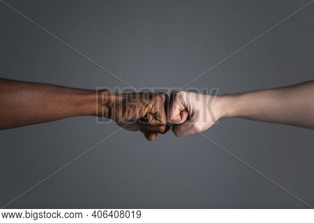 Close Up Of White Skinned Man And Dark Skinned Man Doing A Fist Bump Isolated On Gray Background Wit