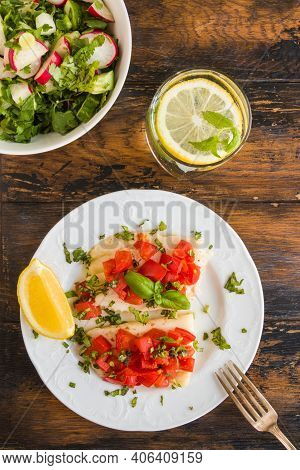 Halibut Fish Fillet Baked With Tomatoes On White Plate. Salad With Radish And Cucumber In Bowl. Wood