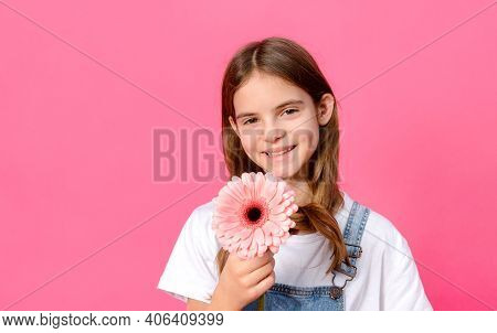 1 White Girl 10 Years Old In A White Jacket With A Pink Gerbera Flower In Her Hands On A Pink Backgr