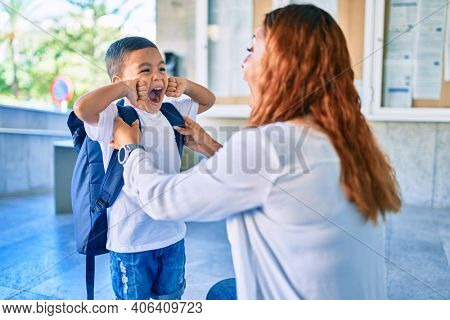 Adorable latin student boy and mom at school. Mother preparing kid putting up backpack.