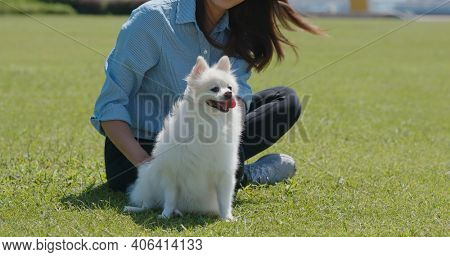 Woman cuddle her dog and sit on the green lawn