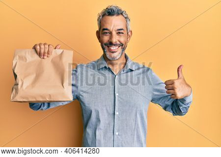 Middle age grey-haired man holding take away paper bag smiling happy and positive, thumb up doing excellent and approval sign