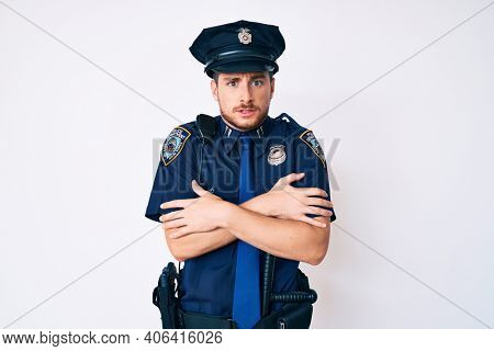 Young caucasian man wearing police uniform shaking and freezing for winter cold with sad and shock expression on face